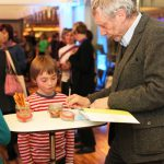 Michael Rosen signs a copy of We're Going on a Bear Hunt for a young fan