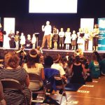 Michael Rosen on stage reading We're Going on a Bear Hunt with children